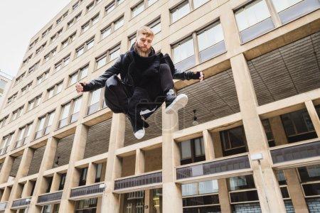 Photo pour Jeune homme barbu élégant sautant dans un contexte urbain - image libre de droit