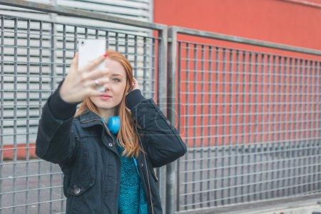 Photo pour Belle jeune fille rousse prenant un selfie dans les rues de la ville - image libre de droit