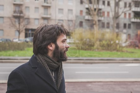 Photo for Young handsome bearded man with coat posing in the city streets - Royalty Free Image