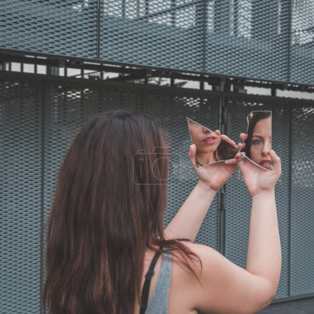 Beautiful girl looking at herself in a broken mirror