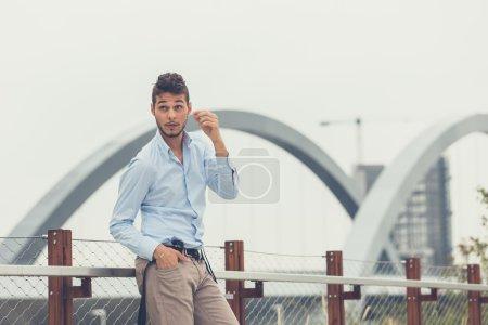 Photo pour Jeune bel homme aux cheveux courts et barbe portant des bretelles et posant dans un contexte urbain - image libre de droit