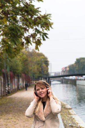 Photo pour Belle jeune fille aux longs cheveux blonds et écouteurs écoutant de la musique dans un contexte urbain - image libre de droit