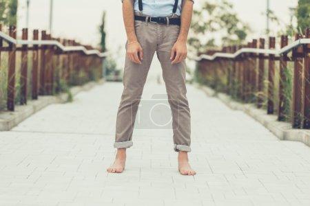 Photo pour Détail d'un jeune homme portant des bretelles et posant dans un contexte urbain - image libre de droit