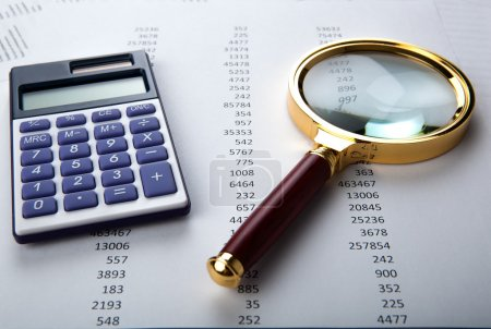 Photo for Work with a magnifying glass, a calculator and papers - Royalty Free Image