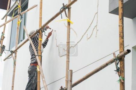 Photo pour Travailleurs de l'échafaudage propagation stuc sur mortier, réparation hom - image libre de droit