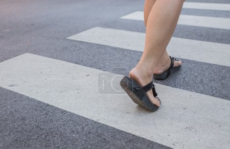 A woman crossing a crosswalk
