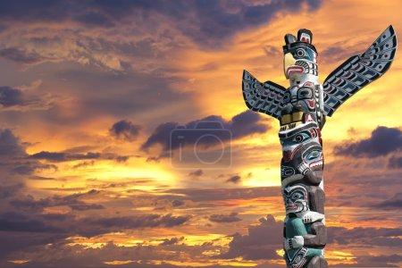 Photo pour Poteau en bois totem isolé dans le fond du coucher du soleil d'or - image libre de droit