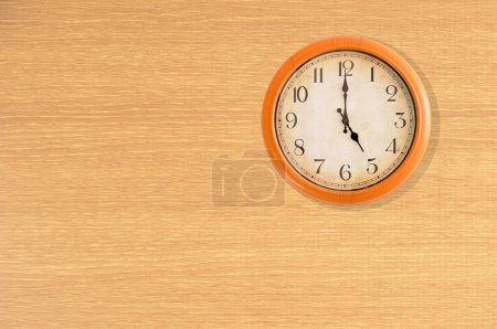 Clock showing 5 o'clock on a wooden wall