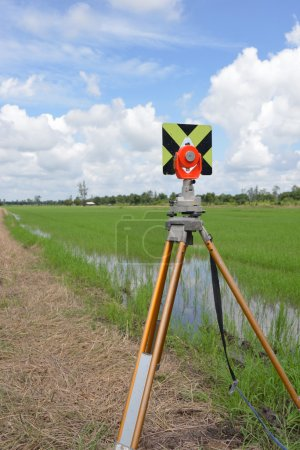 Survey instrument set on a tripod in the field