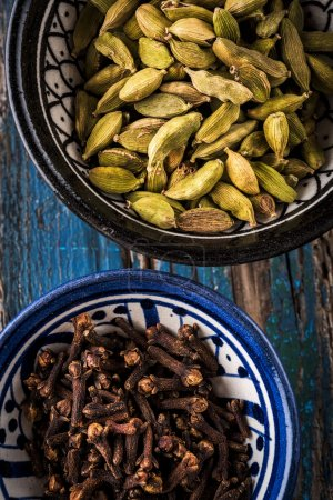 cardamom and cloves in bowls