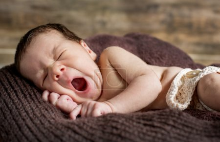 Cute newborn yawns lying on a blanket