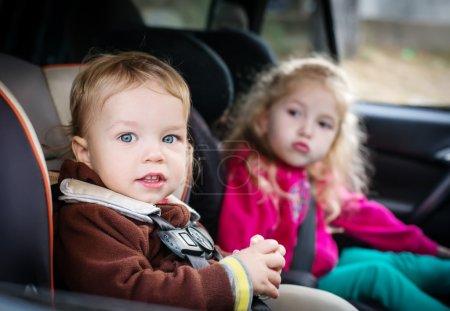 Foto de Lindos niños pequeños en asientos en el coche - Imagen libre de derechos