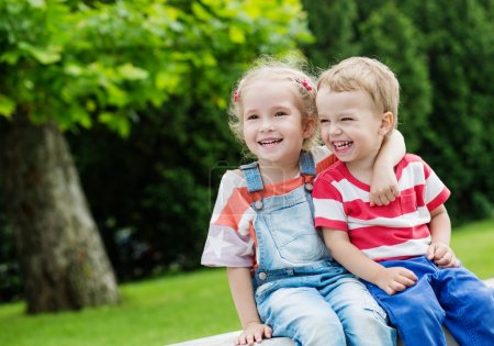 Photo for Happy Toddler brother and sister hugging in summer - Royalty Free Image