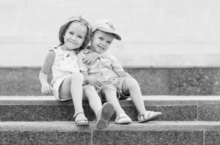 Photo for Happy toddler children sit on the steps outdoors ( black and white ) - Royalty Free Image
