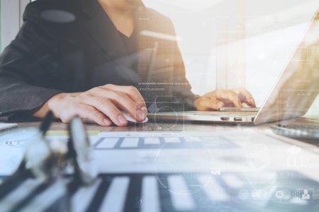 Photo pour Documents d'affaires sur la table de bureau avec ordinateur portable et téléphone intelligent et graphique diagramme numérique d'affaires et homme d'affaires travaillant en arrière-plan - image libre de droit