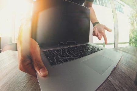 Photo pour Main designer travaillant avec ordinateur portable sur un bureau en bois comme concept de responsive web design - image libre de droit