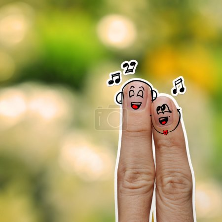 Photo for The happy fingers couple in love with painted smiley and sing a song on flower nature background - Royalty Free Image