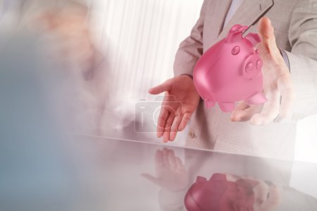 businessman hand shows piggy bank as concept