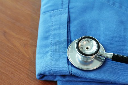 Stethoscope with blue doctor coat on wooden table with shallow D