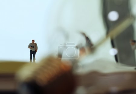 Creative idea concept - miniature photographer with vintage ligh