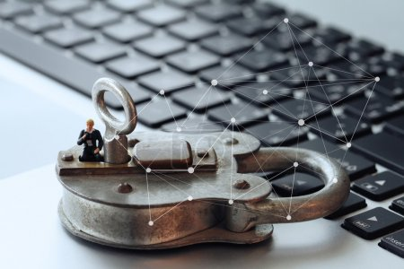 Internet security concept-miniature businessman stand on old key