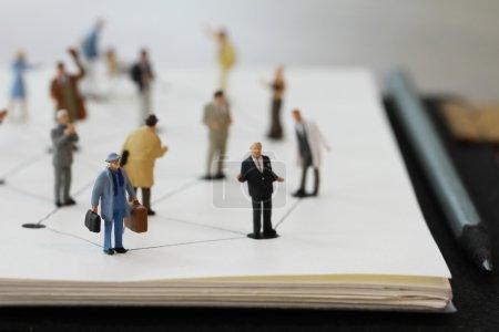 Photo pour Gros plan de personnes miniatures avec diagramme de réseau social sur ordinateur portable ouvert sur bureau en bois comme concept de médias sociaux - image libre de droit