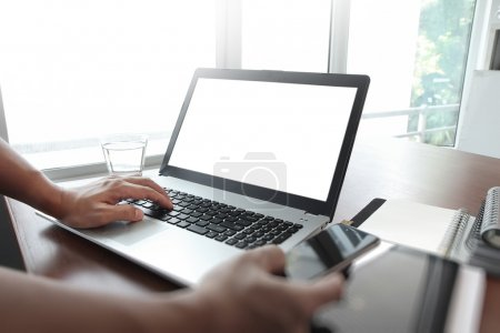 Photo for Businessman hand using blank screen laptop and mobile phone in office - Royalty Free Image