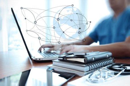 Photo pour Médecin travaillant avec un ordinateur portable dans un bureau d'espace de travail médical et un diagramme de médias de réseau médical comme concept - image libre de droit