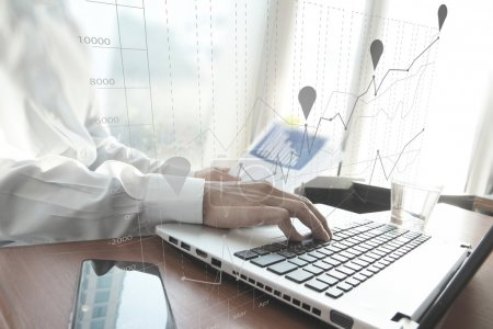 Photo for Business man hand working on laptop computer on wooden desk as concept and graph business diagram - Royalty Free Image