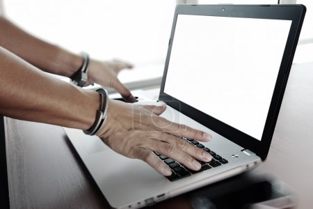 Businessman hand in handcuffs at wooden desk with laptop compute