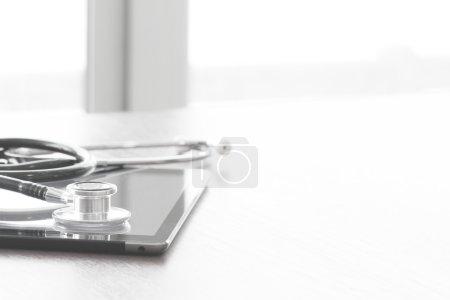 Photo pour Macro studio d'un stéthoscope et tablette numérique sur table en bois espace de copie de fond - image libre de droit