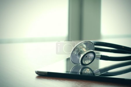 Photo for Studio macro of a stethoscope and digital tablet with shallow DOF evenly matched abstract on wood table background copy space - Royalty Free Image