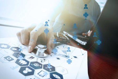 Photo pour Médecin travaillant avec une tablette numérique et un ordinateur portable dans un bureau d'espace de travail médical et un diagramme de médias de réseau médical en tant que concept - image libre de droit