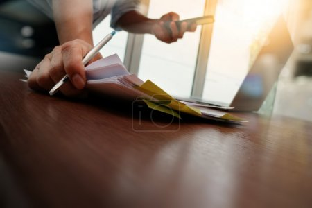 designer hand working and smart phone and laptop on wooden desk