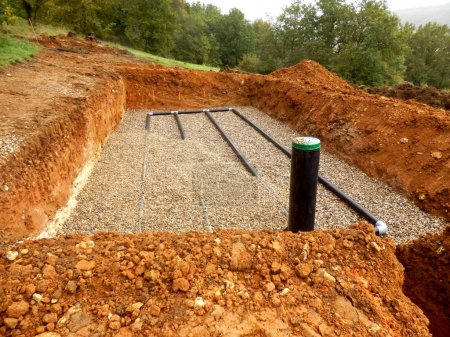 Bottom layer of pipework laid on gravel in the construction of a sand and gravel drainage system