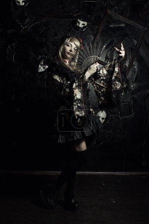 Japanese girl in kimono with fan posing over dark ...