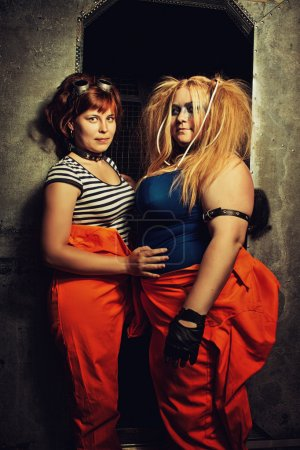Photo for Two pretty girls in orange clothes posing over metallic wall of their prison cell - Royalty Free Image