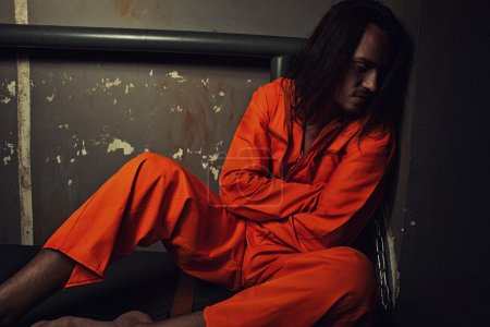Photo for Miserable prisoner in orange clothes sitting on a bed in his cell - Royalty Free Image