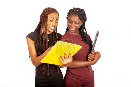 Photo pour Deux beaux étudiants debout sur fond blanc regardant un magazine et tenant un ordinateur portable. - image libre de droit