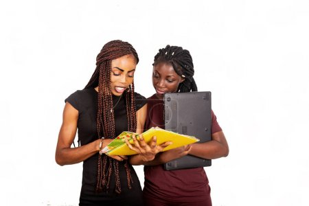 Photo pour Deux beaux étudiants debout sur fond blanc lisant un magazine et tenant un ordinateur portable. - image libre de droit
