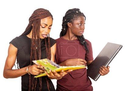 Photo pour Une belle étudiante debout sur un fond blanc feuilletant un magazine pendant que sa petite amie regarde ailleurs tout en tenant un ordinateur portable. - image libre de droit