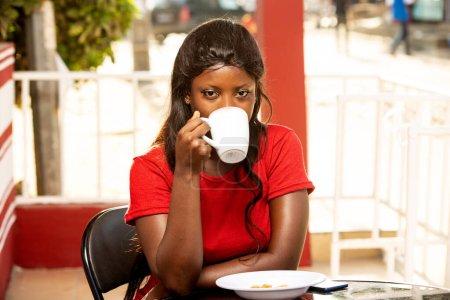 Photo pour Une jeune femme assise devant la cafétéria va boire du thé en regardant ailleurs. - image libre de droit