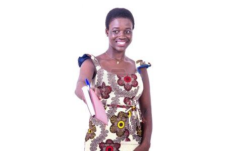 Photo pour Belle jeune femme d'affaires en robe debout sur fond blanc donnant journal intime et détournant les yeux souriant - image libre de droit