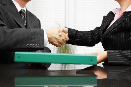 Foto de Empresario está pasando la carpeta con la documentación a su cliente mientras el apretón de manos - Imagen libre de derechos