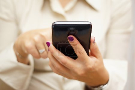 woman is typing on touchscreen on big mobile phone