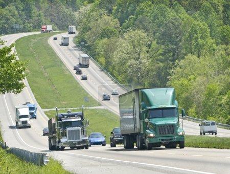 Photo pour Plan horizontal de camions et d'autres véhicules grimpant la colline sur l'autoroute - image libre de droit