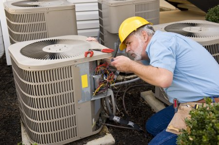 Photo for Mature repairman works on an apartment air conditioning unite - Royalty Free Image