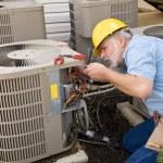 Mature repairman works on an apartment air conditi...