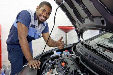 Foto de Lindo mecánico de automóviles sonriendo y dando un pulgar hacia arriba - Imagen libre de derechos