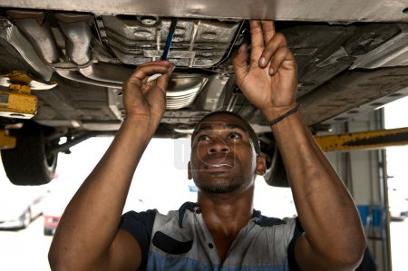 Confident Auto Mechanic Checking Out Vehicle